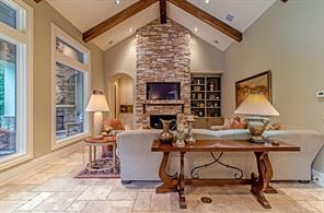 This is the family room, with fireplace and the loggia / summer kitchen through the windows to the left. Soaring vaulted ceiling with beams make it feel so warm and comfortable.