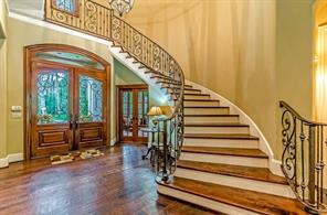 The grand stairway gracefully arches over the study door and front doors. Let's go up and see the rest of the house!
