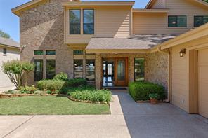 Beautifully landscaped front yard with double entry door at covered front porch.