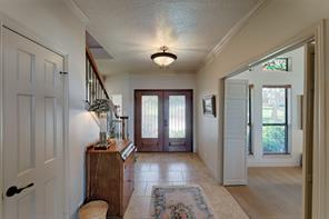 View of front doors from the front entry hall.  Entrance is flanked by staircase, kitchen access hall and game room.