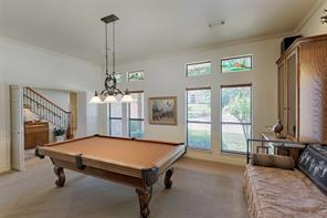 Downstairs game room features high ceilings, stain glass window detail, crown molding and custom built ins.