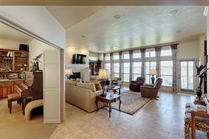 View as you enter the home.  Spacious living room features wall of windows to enjoy the view of Lake Conroe.