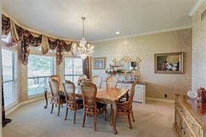 Dining room with lovely chandelier, crown molding and view of Lake Conroe.