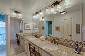 Master bathroom features double sinks, dressing mirror, custom lighting, tile and even a view of the lake!