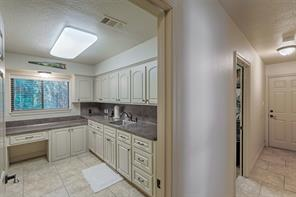 Laundry room features desk, loads of storage, sink and folding area.  Washer and dryer tucked behind custom doors.