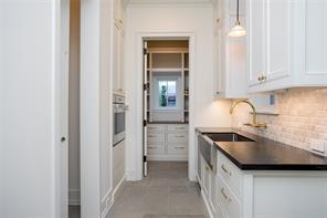 Scullery: Versailles pattern Sandstone floors, leathered soapstone counter, beveled Carrera marble backsplash, stainless steel apron front sink with Waterstone wall mounted unlacquered brass faucet, Sub-Zero beverage refrigerator, stainless steel Wolf convection oven, Wolf warming drawer, views to kitchen garden
