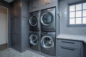 Laundry room : 2 Electrolux washers and dryers, tree top views of front garden