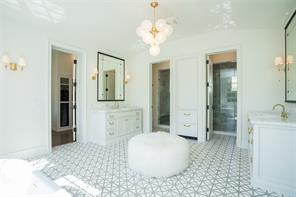 Master Bathroom : White and grey marble floors, brass and milk glass spheres chandelier, 2 pair of brass and glass sconces, white marble counters, porcelain sinks, unlacquered brass faucets, unlacquered brass hardware
