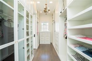 Her closet: White oak floors, extensive built-in hanging space, glass front cabinets, slide-out shelves, chest of drawers with white marble top, vanity area with white marble top and brass hardware.