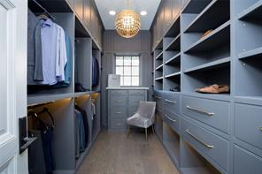 His closet: white oak floors, recessed lighting, abundant hanging space, deep drawers, shelving with LED strip lights, chest of drawers with marble top, window for natural light