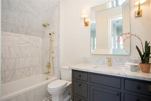 Secondary Bath: Grey and white marble floors, pair of brass sconces, Carrera marble counters, porcelain sink, brass fixture, beveled mirror, built in drawers and cabinets, tub/shower with white marble surround and Carrera marble walls, brass faucet and had spray, Toto toilet