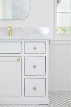 Secondary Bath: white and grey marble mosaic floors, Carrera marble counters, porcelain sink, built in drawers and cabinets with brass and mother of pearl honeycomb pulls, beveled mirror