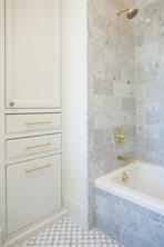 Secondary Bath: Tub/shower with Carrera marble wall, Toto toilet, cabinets with brass pulls