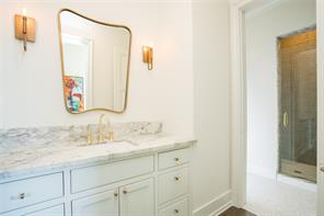 Secondary Bath: porcelain sink vestibule with oak floors, marble counter, brass faucet, brass sconces with Edison bulbs, gold framed mirror.