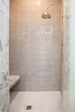 Secondary Bath: Separate toilet and shower room with white and beige oval mosaic tiles, walk-in shower with hand painted geometric tile and brass faucet and hand spray, shared with the game room