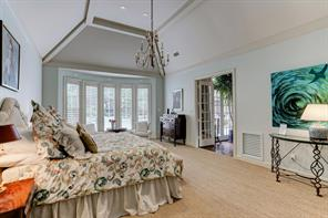 The master bedroom with 12 foot ceiling and a bay window overlooking the private back yard, pool, patio and grounds.
