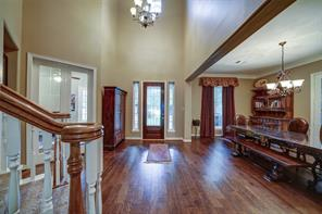 View of formal dining from foyer, kitchen beyond. Hardwood floors continue into dining room with a window view to the front yard and french doors leading to the secondary front porch.