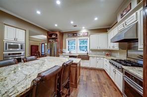 Large, open kitchen is the cook's dream! Oversized island with seating for 5, gas cook top and large farm sink are just a few of the upgrades to this kitchen. The custom back splash continues from the dining room.