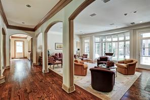 Alternate view of the family room that highlights the arched openings and beautiful wall of windows overlooking the backyard