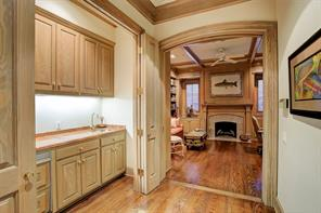 Hallway leading to study and wet bar with folding pocket doors