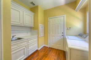 The door goes to the oversized garage. The small door is the laundry chute from above! Very Convenient. Deep sink make clean ups a breeze.