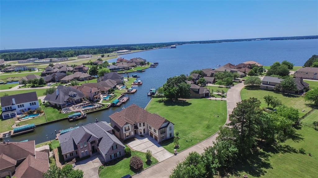 Luxury waterfront home in gated community on Lake Conroe featuring gorgeous lake views & private sunsets from your own yard & 32 x 12 covered balcony! Located on an inlet cove, complete w/bulkhead and covered boat slip with 6000-lb lift, this home affords great easy access to the main lake. Large 5-bedroom home w/over 4800 sf, this home features beautiful custom woodwork/trim, upgraded alder wood cabinetry, gorgeous wood flooring, chef's granite island kitchen w/slate flooring and commercial grade appliances. Great room with soaring ceiling & floor-to-ceiling windows afford incredible lake views and enormous incoming light. First floor master with outdoor patio access. Luxury master bath with dual vanities, makeup counter, separate rain-head shower w/sprayer options & custom dream closet w/fabulous built-ins, Second floor includes 24 x 18 game room, 15 x 15 media room and 4 secondary bedrooms with balcony & lake views. Easy access to I-45, The Woodlands Mall and the new Exxon campus!