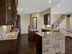 Stone walled kitchen on peninsula of the kitchen with granite countertops.