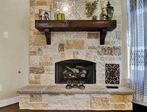 Gas started fireplace with gas logs, wooden mantle, stone, and raised hearth.  Beautiful.