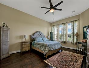 Spacious master bedroom with a lot of natural light, features hard wood floors.