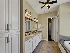 Master bathroom with his and hers lavatories, granite countertops, garden tub and view of the master closet.