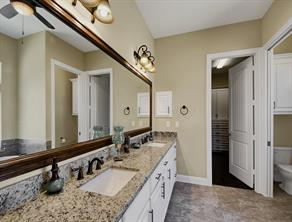 Closeup of the master bathroom countertops, lavatories, decorative hardware and tile flooring.