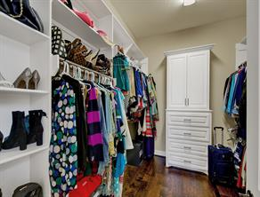 Master closet with tons of built ins, storage, shelving, and hard wood flooring.