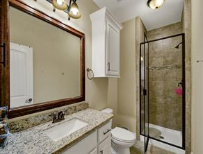 Upstairs bathroom with walk in shower, granite tops and decorative mirror.