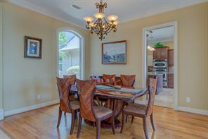 Rich wood flooring, crown molding and arched windows create beautiful ambiance in the Formal Dining Room