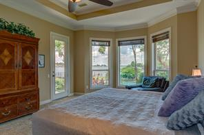 The luxurious Master Suite features far reaching lake views, a tray ceiling along with direct access to the patio & pool