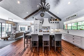 What a great view of the kitchen, and family room to the right.  High ceilings and architectural wood beams make this space so divine.
