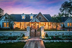 This inviting entry gate with artisan wrought iron archway and carriage light flanked by stone and wrought iron fence, and flowering beds bursting with color.