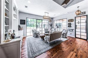 Family room located off the kitchen and features custom windows and doors overlooking the pool and lush open green space behind the home. Custom built-ins with refrigerated beverage drawers add to your enjoyment.