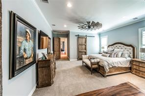 Another view of the master bedroom with custom sliding wood door leading to one of the two spacious master closets.