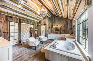 Just when you think, this home couldn't possibly get any more spectacular, you enter into this amazing master bathroom with reclaimed wood ceiling and walls and sliding barn door style accent doors.  Wood flooring, designer lighting and custom cabinetry all come together perfectly in this space.