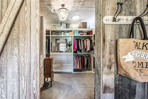 Master closet #2, with custom built in's, chandelier and lush carpeting.