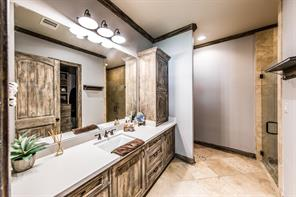 Ensuite bathroom off of the bedroom is spacious and features travertine floors and glass enclosed shower.