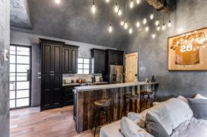 Guest cottage with custom made light fixture that perfectly highlights this well done space complete with wood flooring, custom cabinetry, reclaimed wood backed bar and Venetian plaster walls.