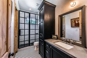 You will love the high end selections in the guest cottage bathroom; stone countertop with undermount sink, subway tile surround shower with custom made glass door enclosure and mosaic tiled floor.