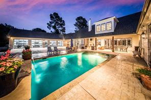 Dusk view of this amazing space that is perfect for a quiet evening or large gathering. Don't miss the covered back patio with cozy fireplace and grill area.