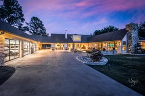 This spectacularly designed property is like no other. Expansive driveway with covered motor court, custom glass garage doors display the finished 4 car bay garage and workshop is on your left.  Covered patio, fireplace, pool and fire pit are on your right and wide open space surrounds you. You will feel like you are miles away from Houston in your own secluded country retreat.