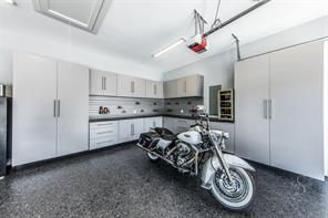 Meticulous isn't typically associated with garage space but it is in the workshop area with epoxy coated floors, smart cabinetry and beverage fridge