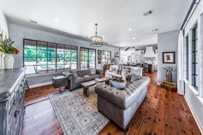 To the left of the entry is this lovely great room, with wood floors, venetian plaster walls, lovely drapery, designer lighting all over looking the pool, patio and wonderful green space.