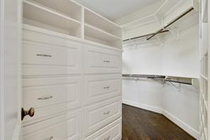 This wrap around, walk-in closet features custom shelving and built-in storage.