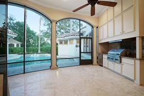 Screened outdoor kitchen equipped with Thermador grill, vent hood, ice maker and generous amount of storage space.
